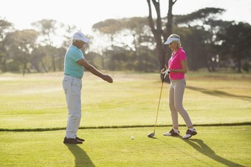 Side view of mature male golf player teaching woman
