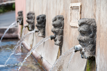 Fountain with lava stone mascarons in one small village at the bottom of Mount Etna, Sicily