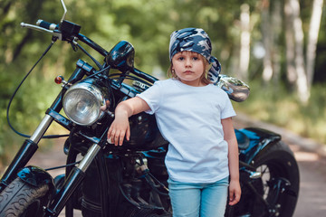 Little girl in a white T-shirt and bandana standing near  motorcycle