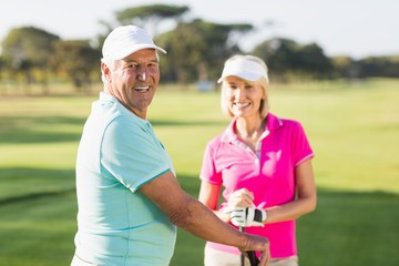 Portrait of happy mature golf player couple