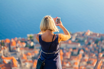 Female traveller make a panoramic photo of the old city of Dubrovnik from the mountain to her phone for Instagram or other social networks. Travel to Croatia. Summer vacation.