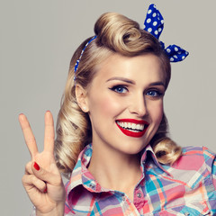 woman, showing two fingers or victory gesture, dressed in pin-up