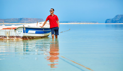 man standing in the sea near the boat. man wearing in red polo shirt and sunglass
