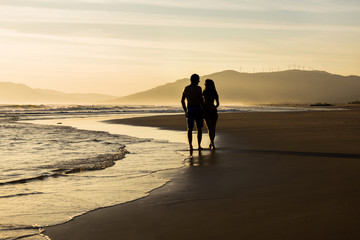 Lovers at sunset holding and walking on a beach silhouettes