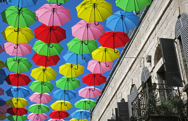 Flying umbrellas in street festival by apartment balcony