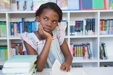 Schoolgirl sitting on table and reading book in library