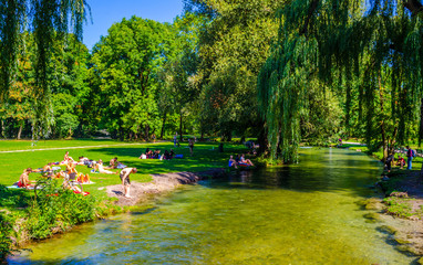 Staande foto Los Angeles People are sunbathing and having a picnic next to an artificial creeking inside of the english garden in bavarian city munich