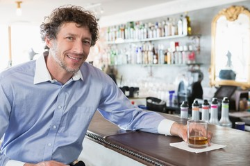 Happy man holding a glass of alcohol