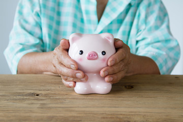 Senior woman hand covering piggy bank