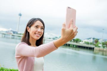 Woman taking selfie by mobile phone in Macau