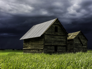Sunny old barn in front of a storm