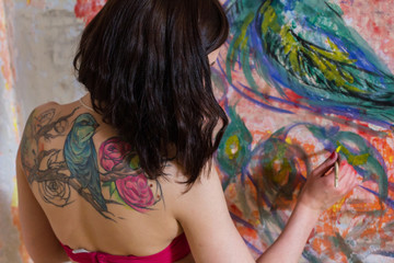 beautiful girl artist paints on the wall