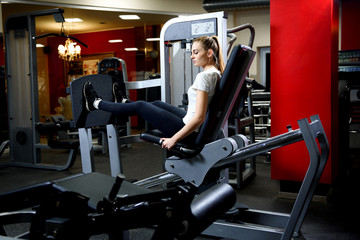 An attractive girl working our on a huge training simulator in a gym.Sportive woman using weights press machine for legs at gym.Pretty brunette exercising in simulator. Working her quads at machine.