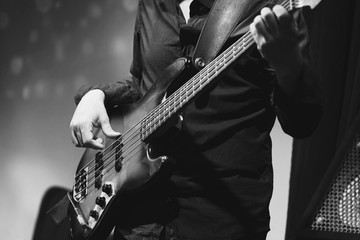 Rock and roll music, bass guitar player closeup