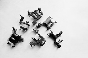 Set of different machines for tattoo at white background. Black and white photo