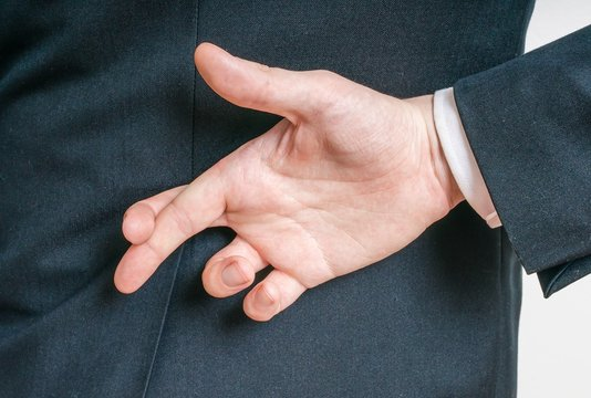 Businessman has crossed fingers behind his back. Good luck or dishonesty concept.