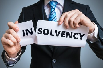 Debt relief concept. Businessman is tearing paper with insolvency to make solvency word.
