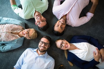 Business team lying on the floor with head together