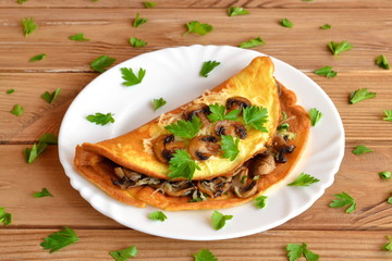 A tasty omelet with mushrooms, cheese and parsley. Stuffed omelet on a plate and on a wooden table. Eggs recipe. Quick vegetarian breakfast idea