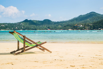 Lounge chairs on a tropical beach at summer.