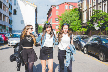 Three young beautiful caucasian millennials women walking outdoor in the city, hugging and talking - friendship, happiness, serene concept