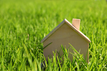 Image of vintage wooden toy house in the grass