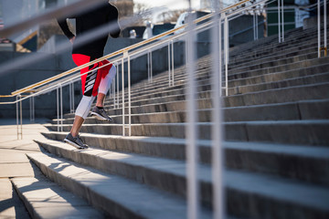Neck down view of young man training, running up city stairs