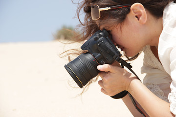 brunette girl in sunglasses and a white blouse takes pictures of something on the background of the desert