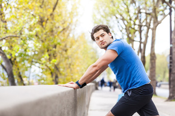 Young man exercising outdoors, leaning against wall, stretching