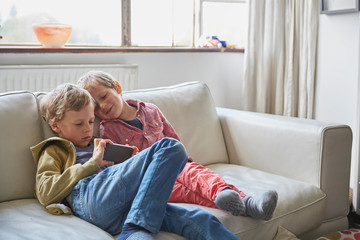 Two boys sitting on sofa looking at phone
