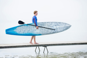 Young man carrying stand up  paddleboard along pier on misty lake Pilsensee, Germany