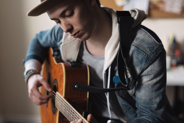 Young man at home, playing guitar