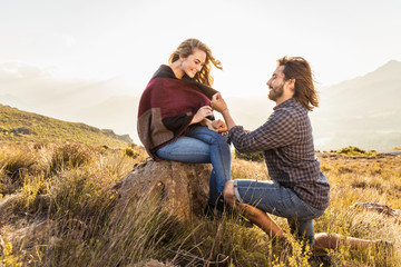Man proposing to woman in meadow