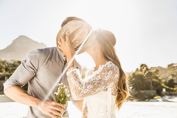 Couple kissing, hiding behind hat
