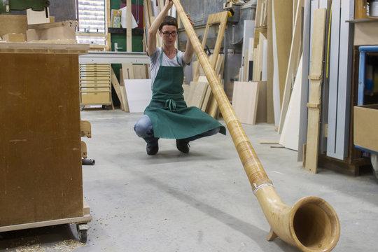 Woman in workshop checking alphorn