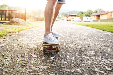 Legs of a man standing on skateboard