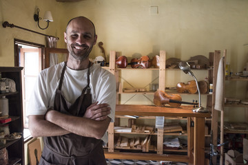 Portrait of smiling luthier in his workshop