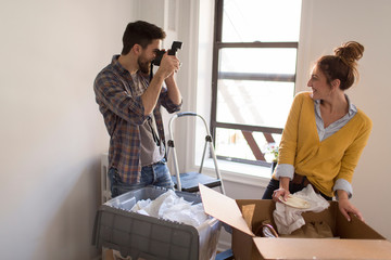 Moving house: Young couple unpacking, young man photographing young woman