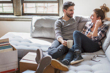 Moving house: Young couple relaxing on sofa surrounded by cardboard boxes