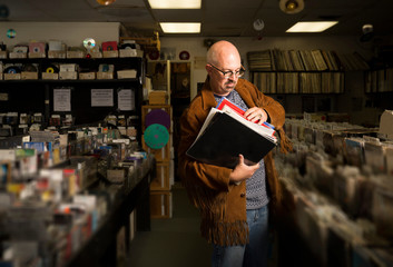 Mature man in record shop, sorting through records
