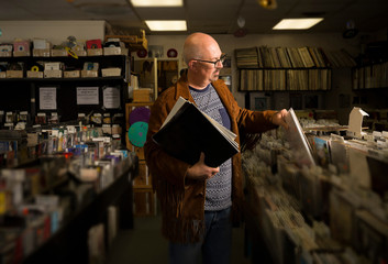 Mature man in record shop, filing records