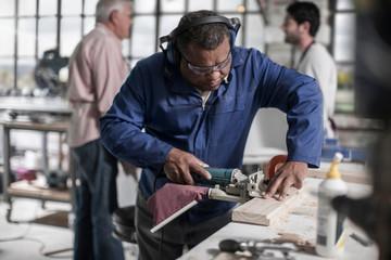 Carpenter using sander in wood workshop