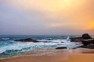 Landscape sunset on rocky tropical beach.