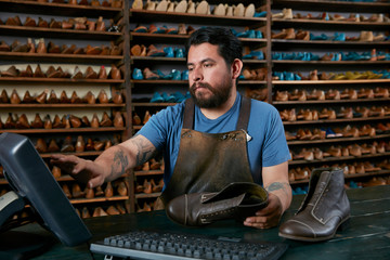 Male cobbler making invoice for boots in traditional shoe shop