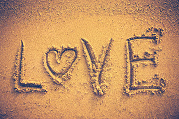 Text LOVE handwritten on seashore sand. Vignette and vintage tone