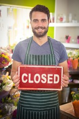 Male florist holding closed signboard at his flower shop