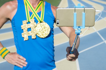 Hashtag gold medal athlete standing at running track taking a photo on his mobile phone with selfie stick