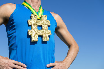 Athlete with hashtag gold medal hanging from Brazil colors green and yellow ribbon standing with hands on hips against bright blue sky