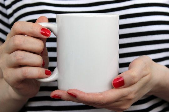 Girl is holding white cup in hands.