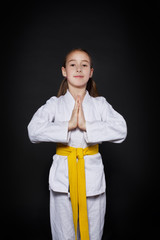 Child girl in karate suit with yellow belt show stance